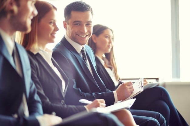 uomo-d-affari-sorridente-in-un-convegno_1098-571